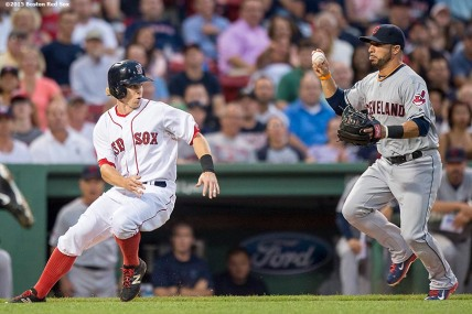 """Boston Red Sox second baseman Brock Holt gets caught in a run down by third baseman Mike Aviles during the first inning of a game against the Cleveland Indians at Fenway Park in Boston, Massachusetts Tuesday, August 18, 2015."""
