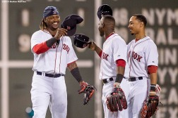 """Boston Red Sox left fielder Hanley Ramirez, center fielder Mookie Betts, and right fielder Rusney Castillo high five after defeating the Cleveland Indians at Fenway Park in Boston, Massachusetts Tuesday, August 18, 2015."""