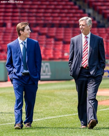 """Newly appointed Boston Red Sox President of Baseball Operations Dave Dombrowski walks on the field with his son Landon at Fenway Park in Boston, Massachusetts Wednesday, August 19, 2015."""