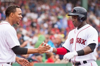 """Boston Red Sox shortstop Xander Bogaerts high fives right fielder Rusney Castillo during the sixth inning of a game against the Kansas City Royals at Fenway Park in Boston, Massachusetts Sunday, August 23, 2015."""