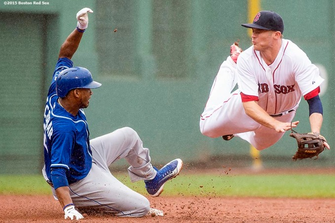 """Bosotn Red Sox second baseman Josh Rutledge dives for an overthrown ball during the sixth inning of a game against the Kansas City Royals at Fenway Park in Boston, Massachusetts Sunday, August 23, 2015."""