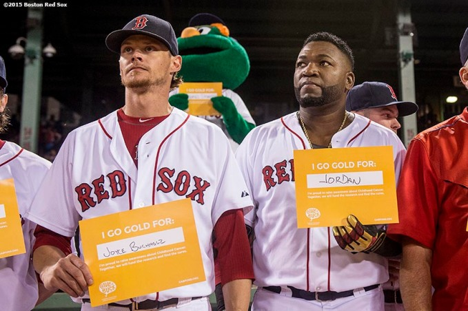 """Boston Red Sox pitcher Clay Buchholz and designated hitter David Ortiz hold up signs during a a childhood cancer awareness ceremony during the third inning of a game between the Boston Red Sox and the New York Yankees at Fenway Park in Boston, Massachusetts Tuesday, September 1, 2015."""