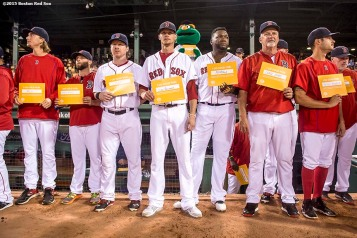"""Members of the Boston Red Sox hold up signs during a a childhood cancer awareness ceremony during the third inning of a game between the Boston Red Sox and the New York Yankees at Fenway Park in Boston, Massachusetts Tuesday, September 1, 2015."""