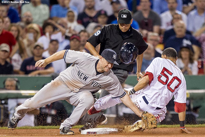 """Boston Red Sox center fielder Mookie Betts is tagged out as he attempts to steal third base during the eighth inning of a game against the New York Yankees at Fenway Park in Boston, Massachusetts Tuesday, September 1, 2015."""