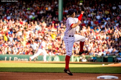 """""""Boston Red Sox third baseman Brock Holt jumps as he fields a ground ball during the fourth inning of a game against the Philadelphia Phillies at Fenway Park in Boston, Massachusetts Saturday, September 5, 2015."""""""