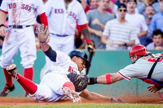 """""""Boston Red Sox shortstop Xander Bogaerts slides into home plate as he scores on an error after an RBI triple during the fourth inning of a game against the Philadelphia Phillies at Fenway Park in Boston, Massachusetts Saturday, September 5, 2015."""""""