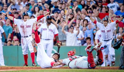 """Boston Red Sox shortstop Xander Bogaerts slides into home plate as he scores on an error after an RBI triple as third baseman Brock Holt, designated hitter David Ortiz, and center fielder Mookie Betts react during the fourth inning of a game against the Philadelphia Phillies at Fenway Park in Boston, Massachusetts Saturday, September 5, 2015."""