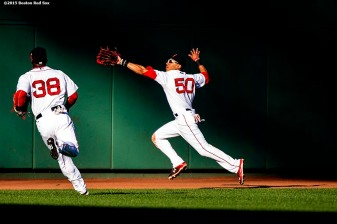 """""""Boston Red Sox left fielder Rusney Castillo and center fielder Mookie Betts reach to catch a fly ball during the sixth inning of a game against the Philadelphia Phillies at Fenway Park in Boston, Massachusetts Saturday, September 5, 2015."""""""