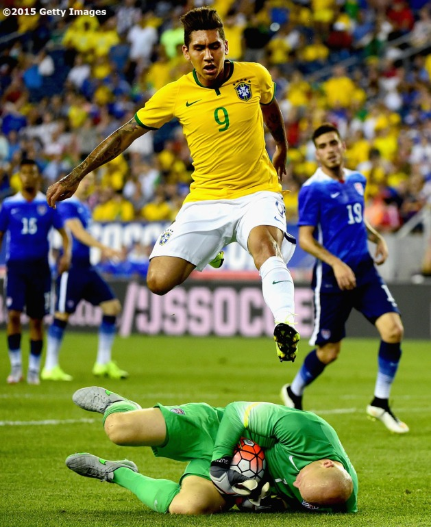 FOXBORO, MA - SEPTEMBER 08: Firmino #9 of Brazil jumps over Brad Guzan #1 of the United States during an international friendly at Gillette Stadium on September 8, 2015 in Foxboro, Massachusetts. (Photo by Billie Weiss/Getty Images)