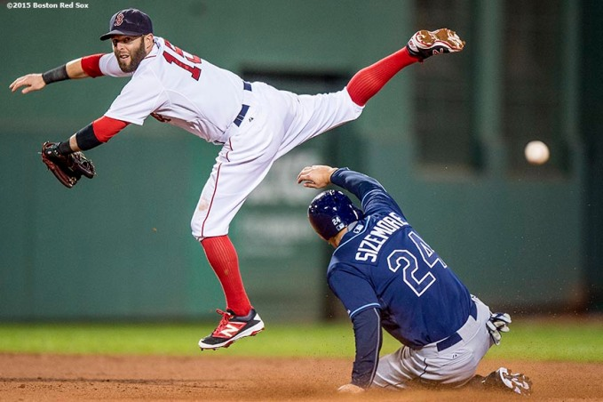 """Boston Red Sox second baseman Dustin Pedroia reaches for an overthrown ball as outfielder Grady Sizemore slides into second base during the seventh inning of a game against the Tampa Bay Rays at Fenway Park in Boston, Massachusetts Monday, September 21, 2015."""