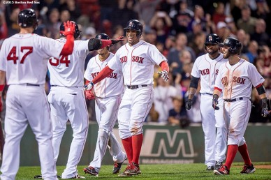 """Boston Red Sox shortstop Xander Bogaerts hugs designated hitter David Ortiz alongside second baseman Dustin Pedroia, center fielder Jackie Bradley Jr., and right fielder Mookie Betts after hitting a go ahead grand slam during the eighth inning of a game against the Tampa Bay Rays at Fenway Park in Boston, Massachusetts Monday, September 21, 2015."""