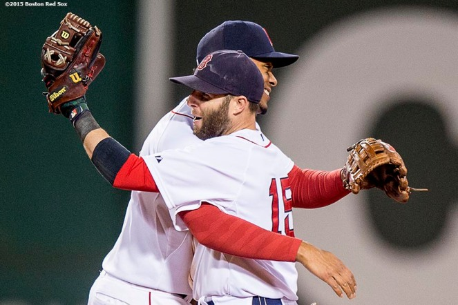 """Boston Red Sox shortstop Xander Bogaerts hugs second baseman Dustin Pedroia after the last out of a game against the Tampa Bay Rays at Fenway Park in Boston, Massachusetts Monday, September 21, 2015."""