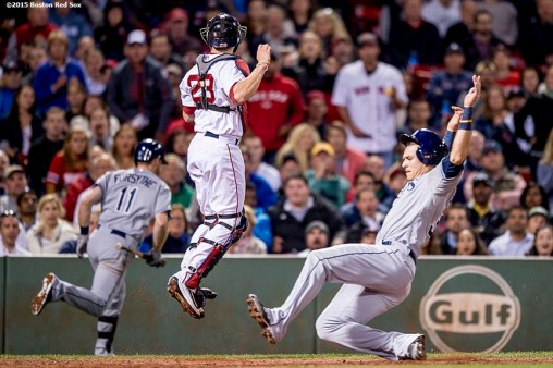 """Boston Red Sox catcher Blake Swihart jumps for an overthrown ball as third baseman Evan Longoria scores during the sixth inning of a game against the Tampa Bay Rays at Fenway Park in Boston, Massachusetts Tuesday, September 22, 2015."""