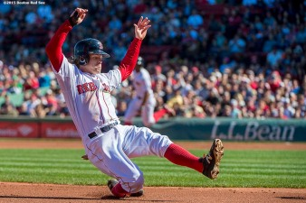 """Boston Red Sox second baseman Brock Holt slides into third base during the first inning of a game against the Baltimore Orioles at Fenway Park in Boston, Massachusetts Sunday, September 27, 2015."""
