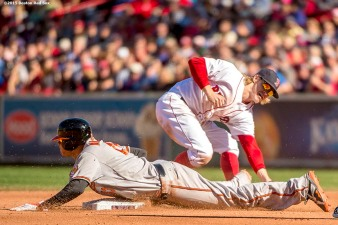 """Boston Red Sox second baseman Brock Holt applies a tag on third baseman Manny Machado as he steals during the sixth inning of a game against the Baltimore Orioles at Fenway Park in Boston, Massachusetts Sunday, September 27, 2015."""