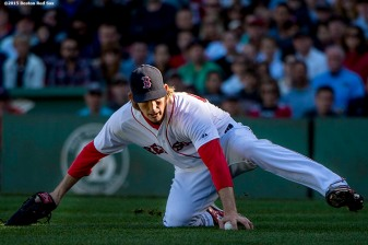 """Boston Red Sox pitcher Henry Owens slides to field a ground ball during the sixth inning of a game against the Baltimore Orioles at Fenway Park in Boston, Massachusetts Sunday, September 27, 2015."""