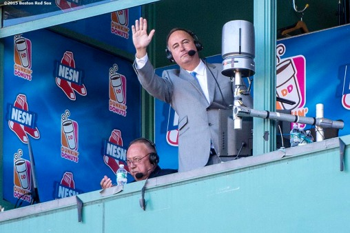 """NESN Broadcaster Don Orsillo waves to the crowd from the booth as he is honored during his last game with NESN during a game between the Boston Red Sox and the Baltimore Orioles at Fenway Park in Boston, Massachusetts Sunday, September 27, 2015."""