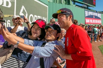 """Pitcher Koji Uehara poses for a selfie photograph during on-field photo day before a game between the Boston Red Sox and the Baltimore Orioles at Fenway Park in Boston, Massachusetts Sunday, September 27, 2015."""