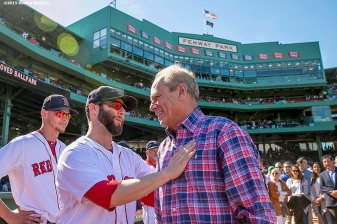 """Boston Red Sox President & CEO Larry Lucchino is congratulated by second baseman Dustin Pedroia during a tribute ceremony for Larry Lucchino before a game between the Boston Red Sox and the Baltimore Orioles at Fenway Park in Boston, Massachusetts Sunday, September 27, 2015."""