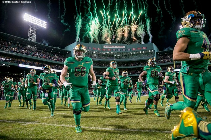 """Fireworks explode as members of Notre Dame run onto the field during the Shamrock Series Football at Fenway game against Boston College at Fenway Park in Boston, Massachusetts Saturday, November 21, 2015."""