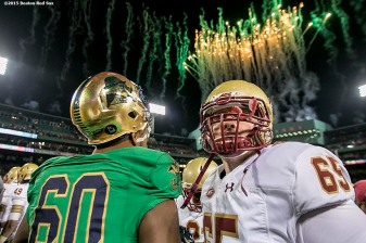 """Members of Notre Dame and Boston College shake hands as fireworks explode over the facade after the Shamrock Series Football at Fenway game at Fenway Park in Boston, Massachusetts Saturday, November 21, 2015."""