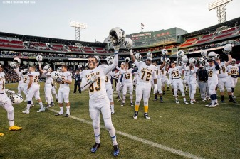 """Members of the Xaverian Brothers High School football team raise their helmets before a game against St. John's Preparatory School at Fenway Park in Boston, Massachusetts Wednesday, November 25, 2015."""
