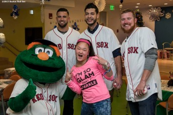 """Boston Red Sox infielder Deven Marrero and pitchers Noe Ramirez and Robbie Ross Jr. and mascot Wally the Green monster pose for a photograph with a patient at Boston Children's Hospital during the Holiday Caravan in Boston, Massachusetts Wednesday, December 9, 2015."""