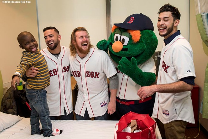"""Boston Red Sox infielder Deven Marrero, pitchers Noe Ramirez and Robbie Ross Jr., and mascot Wally the Green Monster laugh as they visit a patient at Dana Farber Cancer Institute during the Holiday Caravan in Boston, Massachusetts Wednesday, December 9, 2015."""