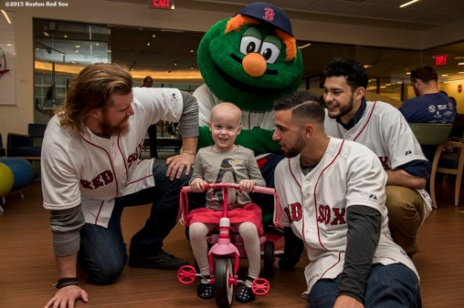 """Boston Red Sox pitcher Robbie Ross Jr., infielder Deven Marrero, pitcher Noe Ramirez and mascot Wally the Green Monster greet a patient at Dana Farber Cancer Institute during the Holiday Caravan in Boston, Massachusetts Wednesday, December 9, 2015."""