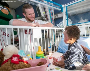 """Boston Red Sox pitcher Craig Kimbrel visits a patient at Shriner's Hospital during the Holiday Caravan in Boston, Massachusetts Friday, December 11, 2015."""