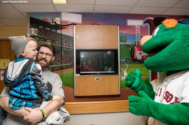 """Boston Red Sox mascot Wally the Green Monster greets a patient at Massachusetts General Hospital during the Holiday Caravan in Boston, Massachusetts Friday, December 10, 2015."""