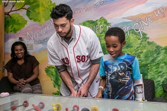 """Boston Red Sox pitcher Noe Ramirez plays foozball with patient at Boston Medical Center during the Holiday Caravan in Boston, Massachusetts Friday, December 10, 2015."""
