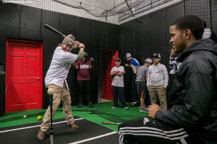 """Boston Red Sox pitcher Robbie Ross Jr. takes swings in the cage as kids watch at the Base during the Holiday Caravan in Boston, Massachusetts Friday, December 10, 2015."""