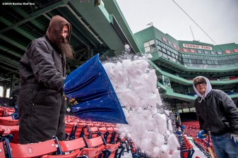 """A worker shovels snow from seats as progress begins on construction of the Big Air ski and snowboard ramp at Fenway Park in Boston, Massachusetts Tuesday, January 19, 2016."""