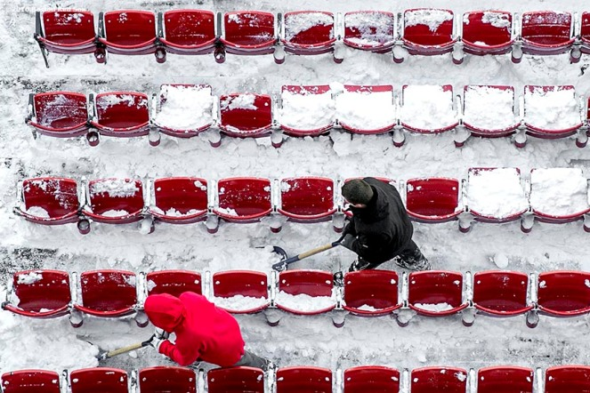 """Workers shovel snow from the seats in preparation for the Big Air at Fenway ski and snowboard competition at Fenway Park in Boston, Massachusetts Monday, January 25, 2016."""