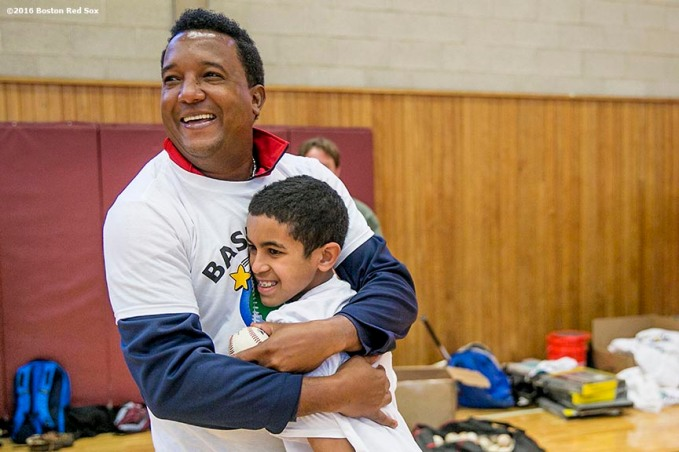 """Former Boston Red Sox pitcher Pedro Martinez hugs a participant during a clinic Dexter High School in Brookline, Massachusetts Monday, February 2, 2016. """
