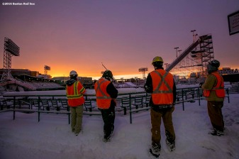 """Workers look on while the sun sets as construction continues on the Polartec Big Air ski and snowboard ramp at Fenway Park in Boston, Massachusetts Friday, February 5, 2016."""