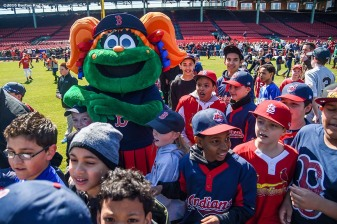 """Fans play in the outfield with Boston Red Sox mascot Tessie during Little League Opening Day at Fenway Park in Boston, Massachusetts Saturday, April 9, 2016."""