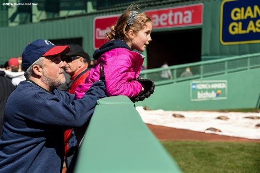"""""""A fan peeks over the bullpen wall during Little League Opening Day at Fenway Park in Boston, Massachusetts Saturday, April 9, 2016."""""""