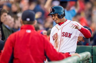 BOSTON, MA - APRIL 20: Mookie Betts #50 of the Boston Red Sox high fives teammates after scoring during the first inning of a game against the Tampa Bay Rays on April 20, 2016 at Fenway Park in Boston, Massachusetts . (Photo by Billie Weiss/Boston Red Sox/Getty Images) *** Local Caption *** Mookie Betts