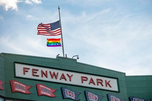 BOSTON, MA - JUNE 14:The Pride flag is flown above the facade along with the American flag at half mast in recognition of the Orlando night club shooting before a game between the Boston Red Sox and the Baltimore Orioles on June 14, 2016 at Fenway Park in Boston, Massachusetts. (Photo by Billie Weiss/Boston Red Sox/Getty Images) *** Local Caption ***