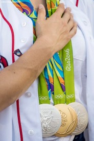 BOSTON, MA - AUGUST 26: Olympic gymnast Aly Raisman holds her hand over her medals before throwing out a ceremonial first pitch before a game against the Kansas City Royals on August 26, 2016 at Fenway Park in Boston, Massachusetts. (Photo by Billie Weiss/Boston Red Sox/Getty Images) *** Local Caption *** Aly Raisman
