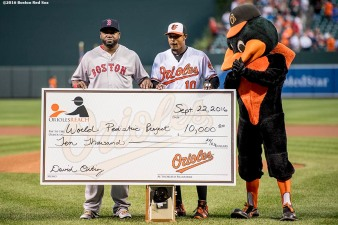 BALTIMORE, MD - SEPTEMBER 22: Adam Jones #10 of the Baltimore Orioles presents a check for the World Pediatric Project to David Ortiz #34 of the Boston Red Sox during an honorary pre game ceremony for Ortiz before a game on September 22, 2016 at Oriole Park at Camden Yards in Baltimore, Maryland. (Photo by Billie Weiss/Boston Red Sox/Getty Images) *** Local Caption *** Adam Jones; David Ortiz