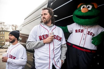 """Boston Red Sox pitchers Robby Scott and Heath Hembree and mascot Wally the Green Monster wait with the van before making an appearance at Codman Academy School as part of The Gift Of Sox and the Holiday Caravan in Dorchester, Massachusetts Thursday, December 8, 2016."""