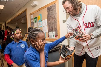 """Boston Red Sox pitcher Heath Hembree hands out Franklin youth baseball gloves to students at Codman Academy School as part of The Gift Of Sox and the Holiday Caravan in Dorchester, Massachusetts Thursday, December 8, 2016."""