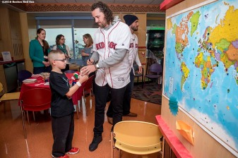 """Boston Red Sox pitcher Heath Hembree greets a patient during a visit to Massachusetts General Hospital as part of the 2016 Holiday Caravan in Boston, Massachusetts Thursday, December 8, 2016."""