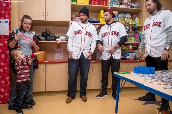 """A young patient plays catch with Boston Red Sox pitcher Robby Scott, infielder Deven Marrero, and pitcher Heath Hembree during a visit to Massachusetts General Hospital as part of the 2016 Holiday Caravan in Boston, Massachusetts Thursday, December 8, 2016."""