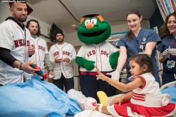 """Boston Red Sox infielder Deven Marrero, pitchers Heath Hembree and Robby Scott, and mascot Wally the Green Monster, pitcher Heath Hembree greet a patient during a visit to Shriners Hospital for Children as part of the 2016 Holiday Caravan in Boston, Massachusetts Thursday, December 8, 2016."""