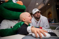 """Boston Red Sox infielder Deven Marrero and mascot Wally the Green Monster play computer games with a patient during a visit to The Jimmy Fund at Dana-Farber Cancer Institute as part of the 2016 Holiday Caravan in Boston, Massachusetts Friday, December 9, 2016."""