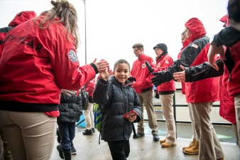 March 27, 2017, Boston, MA: Members of City Year greet students as they arrive as Red Sox hats are given away during a visit to the Hennigan School in Jamaica Plain, Massachusetts Monday, March 27, 2017. (Photo by Billie Weiss/Boston Red Sox)